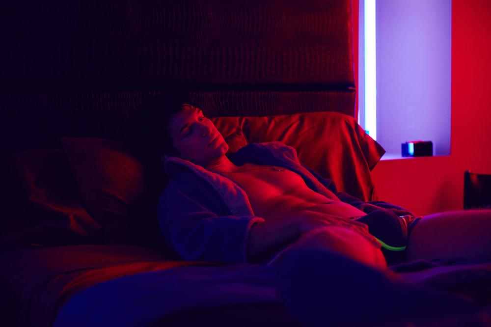 King Cobra: Garrett Clayton steso sul letto in una scena del film