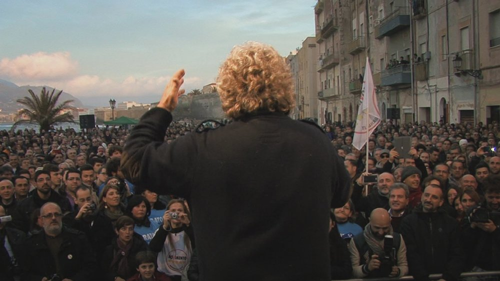 Tutti a casa - Inside Movimento 5 Stelle: Beppe Grillo di spalle durante un comizio in un'immagine del documentario
