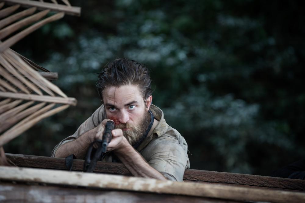Civiltà perduta: Robert Pattinson con un fucile in mano in una scena del film