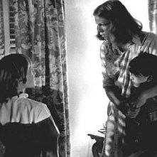 Jamie Lee Curtis con i piccoli Brian Andrew e Kyle Richards controlla che fuori non ci sia nessuna 'ombra della strega' in una scena di Halloween