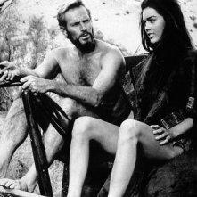 Charlton Heston e Linda Harrison seduti fianco a fianco in una scena de Il pianeta delle scimmie