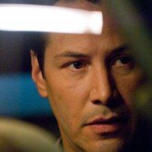 Un primo piano di Keanu Reeves in una scena del film La notte non aspetta