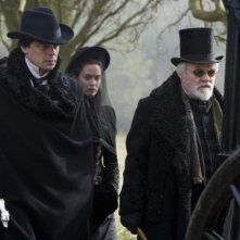 Benicio Del Toro, Anthony Hopkins ed Emily Blunt sullo sfondo in una scena di The Wolf Man