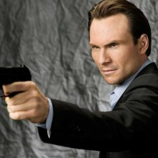 Christian Slater con pistola in una foto promo di My Own Worst Enemy