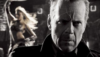 Un primo piano di Bruce Willis con alle spalle Jessica Alba in una scena di Sin City