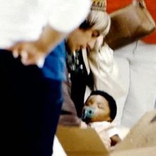 Sacha Baron Cohen nei panni di Bruno in una scena del film in cui ritira il suo bambino 'adottato' all'aeroporto