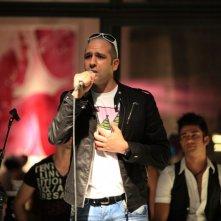Checco Zalone (Luca Medici) al microfono nel film Cado dalle nubi