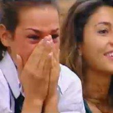 Grande Fratello 10, quarta puntata: Carmen riceve una sorpresa dal fratello. Dietro di lei, Camila sorride.