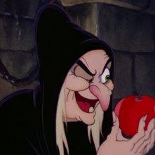 La Strega porge la sua mela avvelenata in una scena del film d\'animazione Biancaneve e i sette nani (1937)