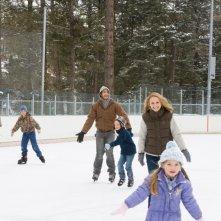 Bailee Madison, Jake Gyllenhaal, Natalie Portman e Taylor Geare pattinano, sorridenti, sul ghiaccio in una scena di Brothers