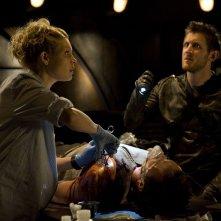 Koz (Primo Allon) fa luce a TJ (Alaina Kalanj) mentre opera Varro (Mike Dopud) nell'episodio Incursion: Part 2 di Stargate Universe
