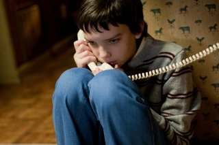 Kodi Smit-McPhee al telefono in una scena del film Let Me In