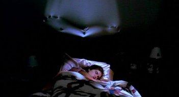 Heather Langenkamp dorme ignara sotto lo sguardo di Freddy Krueger in una scena di Nightmare - Dal profondo della notte