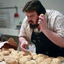 Giuseppe Battiston alle prese con un sacco di panini in una sequenza di Senza arte né parte