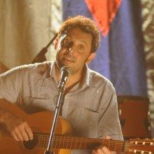Enrico Brignano imbraccia la chitarra in una scena di Faccio un salto all'Avana