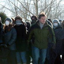 Matt Damon nel thriller Contagion insieme ad un gruppo di persone con il volto coperto
