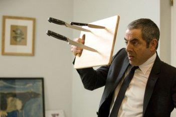 Rowan Atkinson alle prese con un lancio di coltelli in una scena di Johnny English: La Rinascita