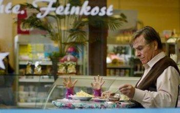 Elmar Wepper e Mercan Türkoglu (sotto il tavolo!) in una divertente scena di Dreiviertelmond