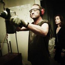 Benoît Poelvoorde alle prese con un trapano in una scena della commedia Mon pire cauchemar insieme a Isabelle Huppert