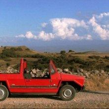 Domenico Montixi osserva la sua automobile in una scena del film Sagràscia