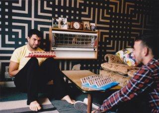 Tom Cullen e Chris New in una scena del dramma sentimentale Weekend alle prese con un gioco da tavolo