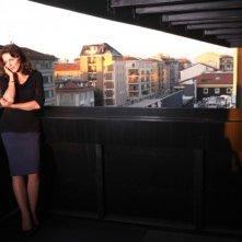 Il mio domani: un'elegante e cupa Claudia Gerini sul balcone parla al telefono in una scena dal film