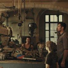 Evangeline Lilly e Hugh Jackman ridanno vita a un robot in una scena di Real Steel con Dakota Goyo