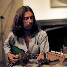 Un giovane George Harrison con la sua chitarra in una scena del film di Martin Scorsese