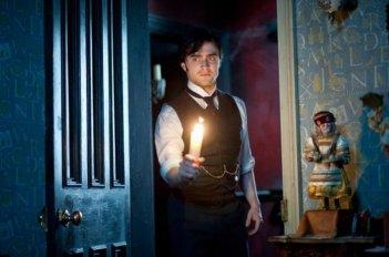 Daniel Radcliffe si aggira per la casa con una candela in una scena del thriller The Woman in Black