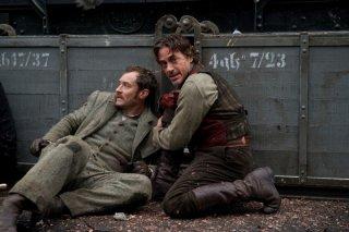 Jude Law e Robert Downey Jr. cercano di ripararsi dal pericolo in una scena di Sherlock Holmes: Gioco di ombre