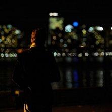 Michael Fassbender di spalle verso lo skyline notturno in un'immagine di Shame