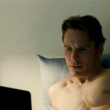 Shame: Michael Fassbender a letto con il suo computer in una scena del film