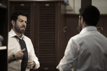 Pierfrancesco Favino, si aggiusta la cravatta in una scena de L'industriale