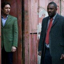Idris Elba e Paul McGann discutono in una scena della seconda stagione di Luther