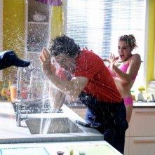 Fabio De Luigi e Claudia Gerini sorpresi da un violento getto d'acqua in una divertente scena di Com'è bello far l'amore