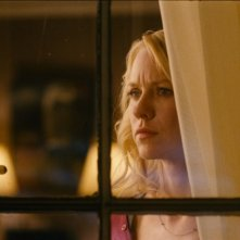 Naomi Watts sospettosa dietro una finestra in una scena di Dream House