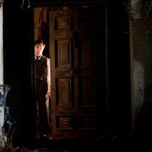 Daniel Radcliffe sospettoso alla porta in una scena del film The Woman in Black