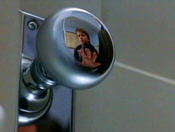 Haley Joel Osment riflesso nella maniglia di una porta in una sequenza de Il sesto senso
