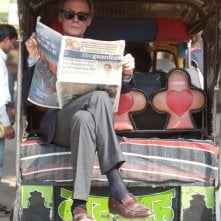 Marigold Hotel: Bill Nighy in una scena del film legge The Guardian a bordo dei una carrozzella indiana