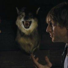 Quella casa nel bosco: Fran Kranz e Kristen Connolly parlano sotto gli occhi di un inquietante lupo imbalsamato in una scena del film