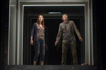 Quella casa nel bosco: Fran Kranz e Kristen Connolly sul monitor di una telecamera che li osserva in una scena del film