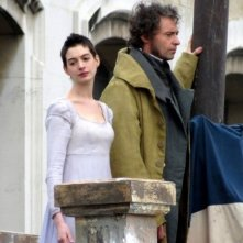Anne Hathaway e Hugh Jackman su un balcone guardano le comparse sul set di Les Misérables