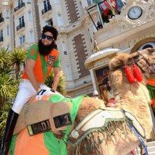 Il dittatore: Sacha Baron Cohen, nei panni dell'ammiraglio generale Shabazz Aladeen, a bordo del suo cammello davanti al Carlton Hotel di Cannes