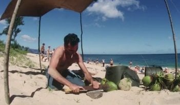 Joaquin Phoenix sbuccia la frutta su una spiaggia in The Master
