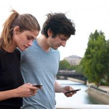 L'amore dura tre anni: Gaspard Proust insieme a Elisa Sednaoui distratti dal cellulare in una scena del film