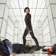 Milla Jovovich contempla i cadaveri di fronte a lei in Resident Evil: Retribution