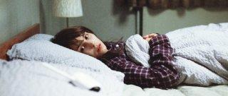 Babycall: Noomi Rapace sdraiata in un letto in una scena del film