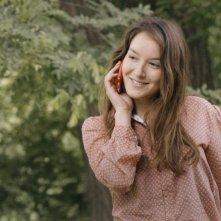 Anaïs Demoustier sorride e parla al telefono in una scena di Elles