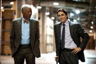 Christian Bale e Morgan Freeman sorridono compiaciuti in una scena di Il cavaliere oscuro - Il ritorno