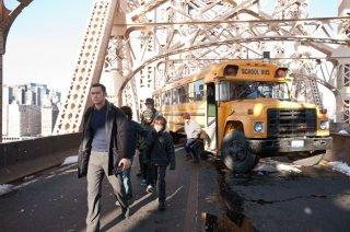 Joseph Gordon-Levitt circondato dai bambini di uno scuolabus in una scena di Il cavaliere oscuro - Il ritorno
